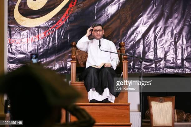 Theologian Imamjamaat of the mosque Meshedi Dadash Haji Shahin hold the Koran on their heads as they pray on Lailat alQadr on May 12 2020 Baku...