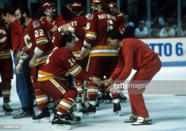 Theoren Fleury of the Calgary Flames celebrates on the ice with teammate Tim Hunter after the Flames defeated the Montreal Canadiens in Game 6 of the...