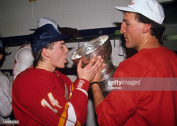 Theoren Fleury of the Calgary Flames looks to drink champagne from the Stanley Cup Trophy as his teammate Tim Hunter helps him hold the Cup after the...