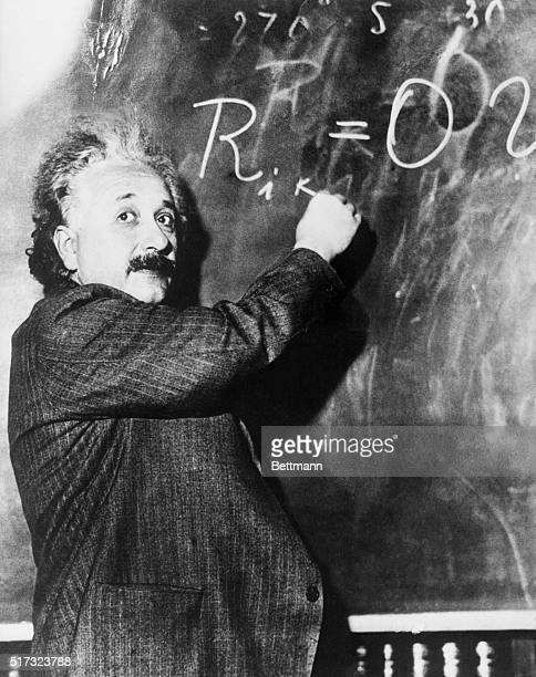 Theoretical physicist Albert Einstein writes a complicated equation on a blackboard He is at the California Institute of Technology for a lecture...