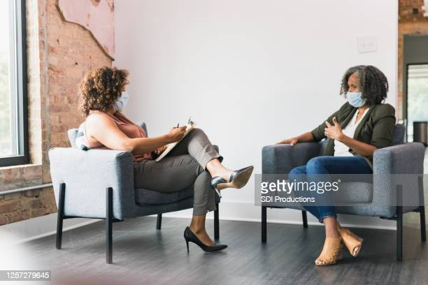 therapist and client wear protective face masks - mental health professional stock pictures, royalty-free photos & images