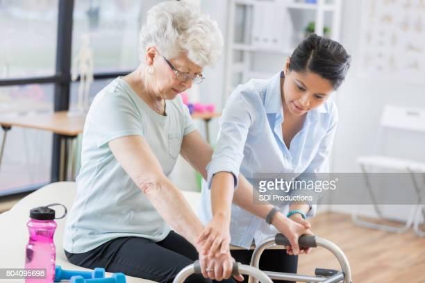 terapeuta ayuda a pacientes mayores a usar el andador - cadera mujer fotografías e imágenes de stock