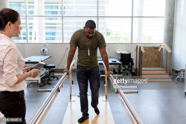 therapist checks posture as mid adult patient walks - black men feet stock photos and pictures