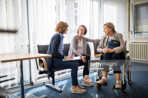 therapist discussing with women in waiting room - disability stock pictures, royalty-free photos & images
