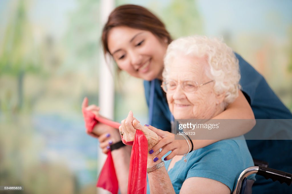 Therapist does physical therapy. Senior woman patient. Arm strengthening. Nurse. : Stock Photo