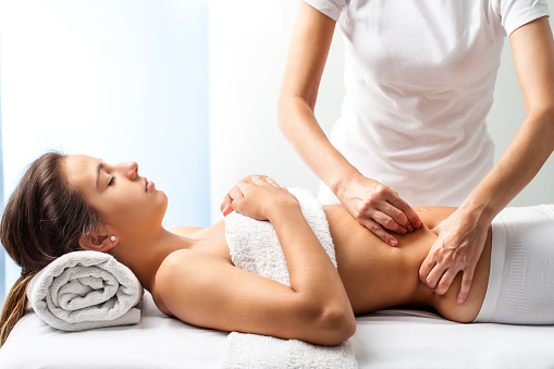 Therapist doing healing massage on female abdomen. 487696618