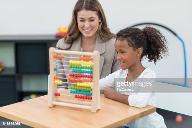 Therapist doing play therapy with young girl