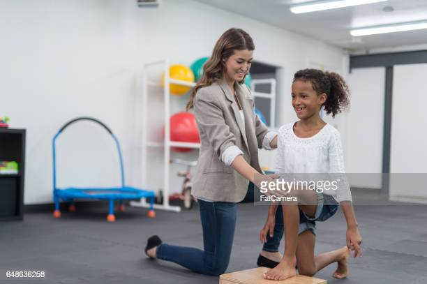 Therapist doing stretching exercise with young African American girl