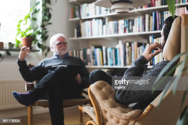 therapist explaining male patient during session at home office - psychiatrist's couch stock pictures, royalty-free photos & images