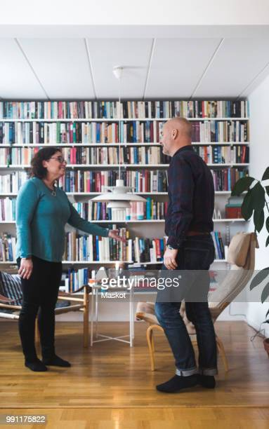 therapist gesturing while talking with patient by bookshelf at home office - psychiatrist's couch stock pictures, royalty-free photos & images