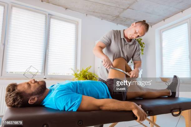 therapist giving leg massage to young man - sports medicine stock pictures, royalty-free photos & images