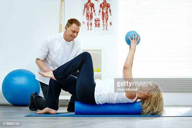 Therapist helping his patient with pilates exercises