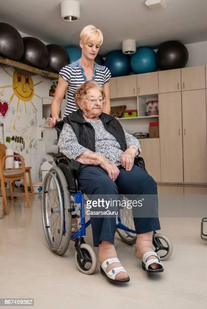 Terapeuta en el hogar de ancianos empujando a mujer Senior en silla de ruedas