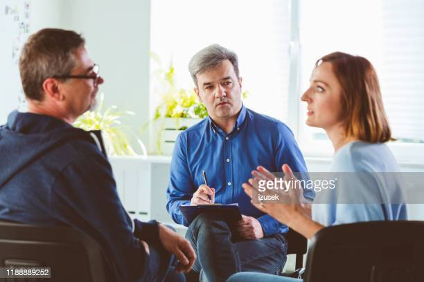 therapist looking at couple arguing during meeting - izusek stock pictures, royalty-free photos & images
