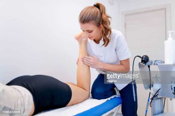 therapist massaging patient's calf muscle on examination table - injured stock pictures, royalty-free photos & images