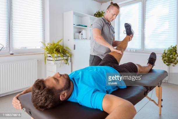 therapist massaging young man at medical center - sports medicine stock pictures, royalty-free photos & images