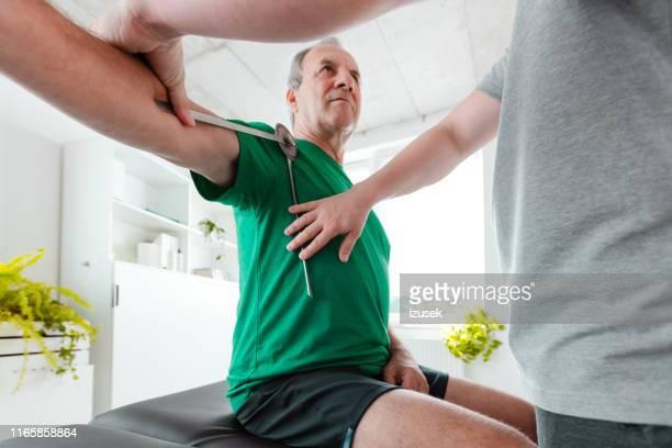 セラピストが分度器でシニア患者の肩を測定する - looking over shoulder ストックフォトと画像
