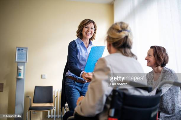 therapist meeting with women in waiting room - cardigan sweater stock pictures, royalty-free photos & images