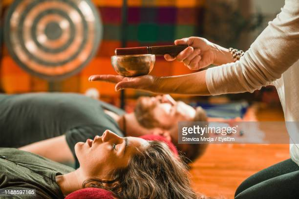 therapist playing rin gong over couple while performing music therapy at spa - rin gong stock pictures, royalty-free photos & images