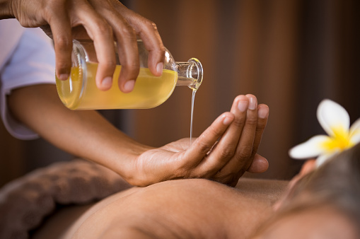 Therapist pouring massage oil at spa 994810170