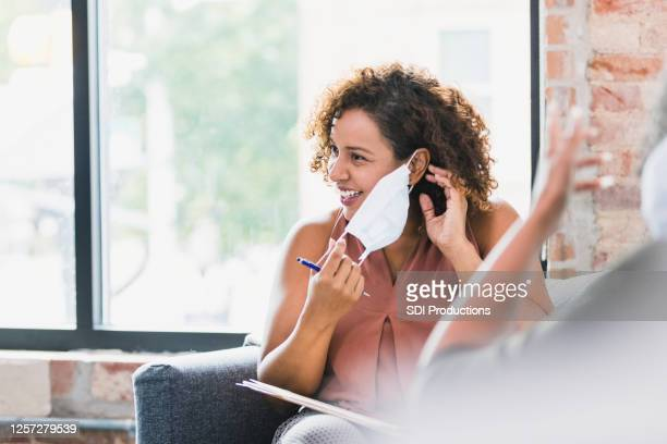 therapist puts on protective face mask before therapy session - removal stock pictures, royalty-free photos & images
