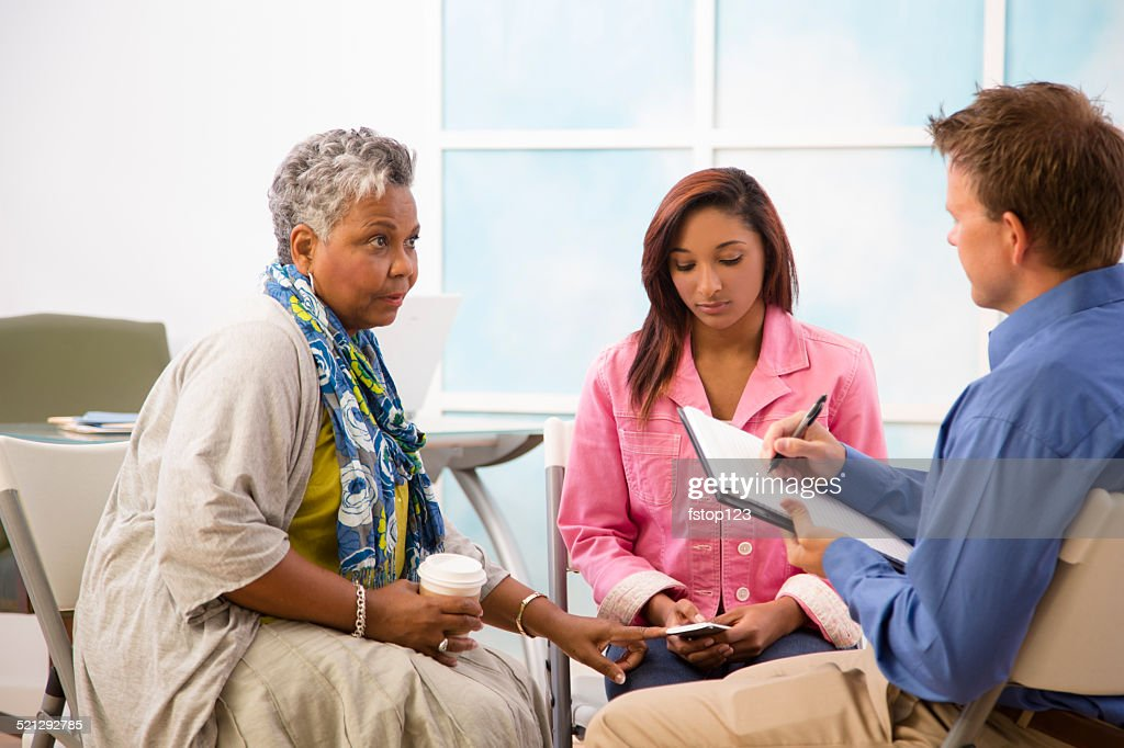 Therapist takes notes in counseling session. Mother, daughter clients. : Stock Photo