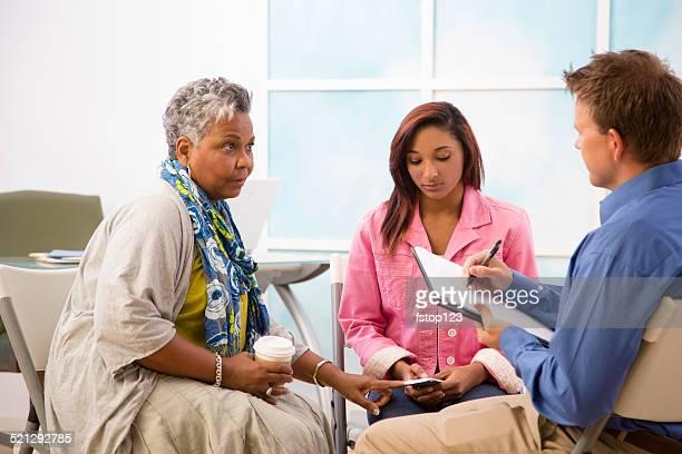 Terapeuta toma notas de orientación de sesiones. Madre hija de los clientes.