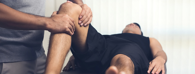Therapist treating injured knee of athlete male patient 952643772