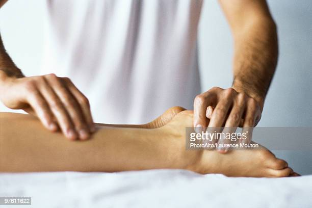 Therapist treating patient's foot with acupressure