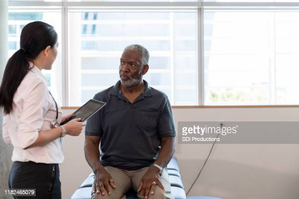 therapist uses digital tablet to diagnose mature patient's problem - outpatient care stock pictures, royalty-free photos & images