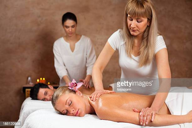 Therapists giving massage to a couple at health spa