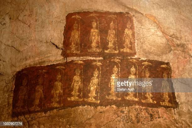 theravada buddhism, ancient wall painting, standing buddha shakyamuni, mudra, varada, gesture of wish-granting, tham pa cave, at nong thang, xieng khouang province, laos, southeast asia - buddhist goddess imagens e fotografias de stock