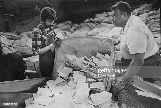 There appears to be no light at the end of the tunnel as Rich Jernandez and Melvin Campbell, right, prepare to sort another bag of mail.;