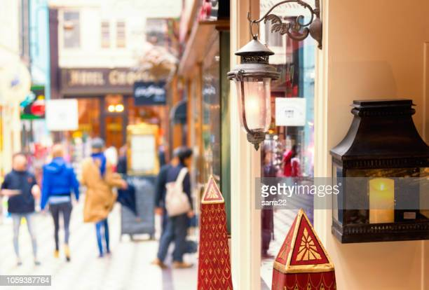 there are people, who are going shoping through passage jouffroy  - shopping area with clothing stores, book stores, jewelers shops, confectionery. - boulevard stock pictures, royalty-free photos & images