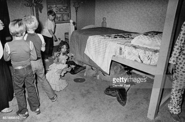 """MAY 4 1981 MAY 5 1981 'There's A Monster In My Closet' Devon Larsen feeds a cookie to the ogre under the bed in a new exhibit """"There's a Monster in..."""