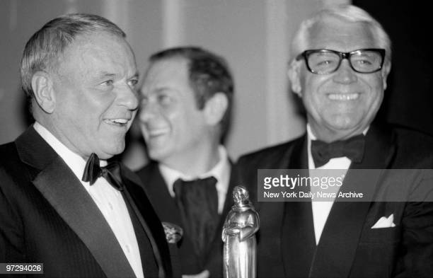 There's a twinkle in the eyes of Ol' Blue Eyes Frank Sinatra as he presents award to Cary Grant as Tony Curtis chuckles in background at Friars Club