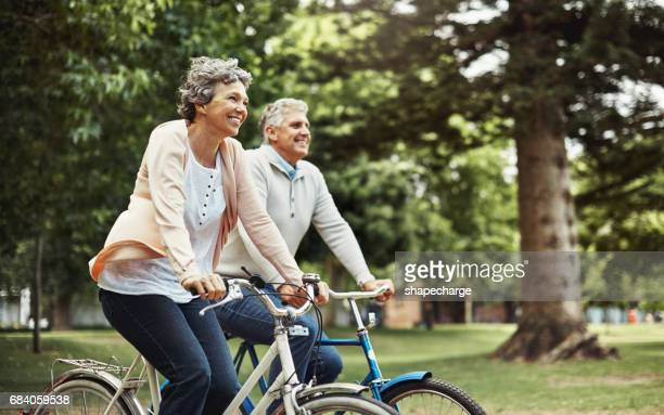 there's nothing better than enjoying a bike ride together - active senior stock photos and pictures