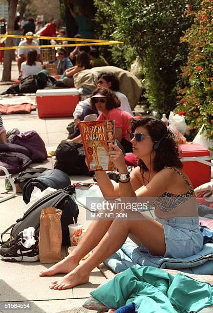 Theresa Feldman of Bradenton Florida reads a magazine while waiting 24 March to enter the bleachers to see the arrival of the nominees for the 68th...