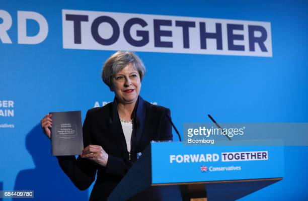 Theresa May UK prime minister and leader of the Conservative Party holds up a copy of the election manifesto titled 'Forward Together' at the launch...