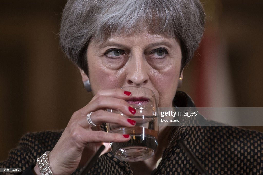 Theresa May, U.K. prime minister, drinks a glass of water during a news conference at number 10 Downing Street following air strikes in Syria, in London, U.K., on Saturday, April 14, 2018. The U.S., U.K. and France hit targets in Syria in retaliation for an apparent chemical weapons attack outside Damascus by Bashar al-Assads regime. Photographer: Will Oliver/Pool via Bloomberg