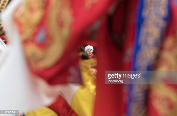 Theresa May UK prime minister is seen between performers as she watches a performance of Chinese opera at the Yellow Crane Tower in Wuhan China on...