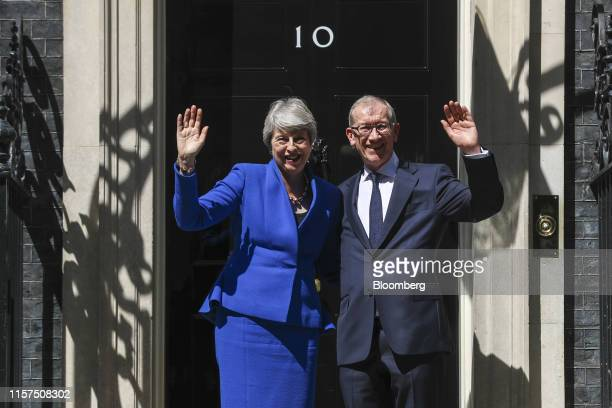 Theresa May UK prime minister left and Philip May her husband wave on the steps before they depart from number 10 Downing Street in London UK on...