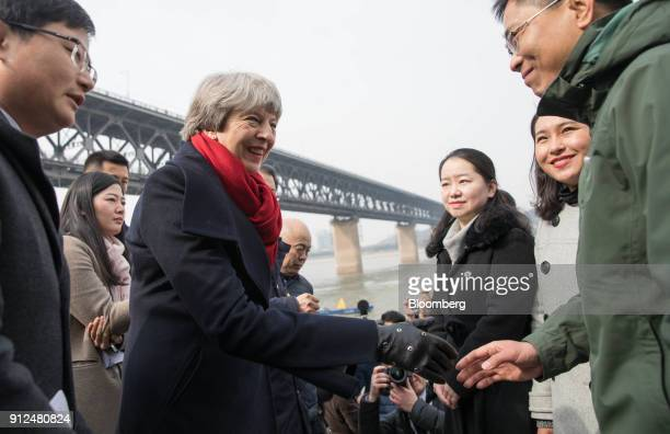 Theresa May UK prime minister left greets environmental experts during a visit to the Yangtze river in Wuhan China on Wednesday Jan 31 2018...