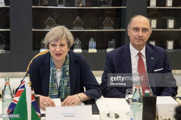 Theresa May UK prime minister left reacts as she attends a meeting with Xavier Rolet chief executive officer of London Stock Exchange Group Plc right...