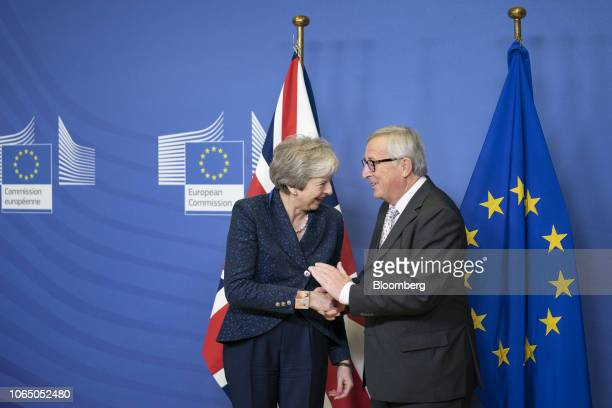 Theresa May UK prime minister left reacts as she shakes hands with JeanClaude Juncker president of the European Commission during a meeting ahead of...