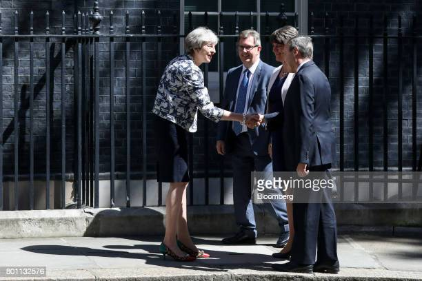 Theresa May UK prime minister left shakes hands with Nigel Dodds deputy leader of the Democratic Unionist Party right as Arlene Foster leader of the...