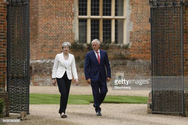 Theresa May UK prime minister left walks with Malcolm Turnbull Australia's prime minister during a meeting at Chequers in Aylesbury UK on Saturday...