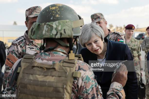 Theresa May UK prime minister looks at a model of a helicopter being held by a soldier at a Jordanian Army Base in Zarqqa Jordan on Monday April 3...