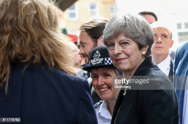 Theresa May UK prime minister right and Cressida Dick the metropolitan police commissioner second right speak with a market stall holder at Borough...