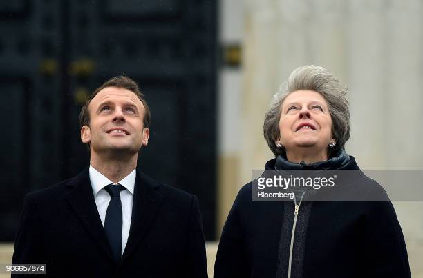 Theresa May UK prime minister right and Emmanuel Macron France's president watch military planes fly overhead during a UKFrance summit meeting at the...